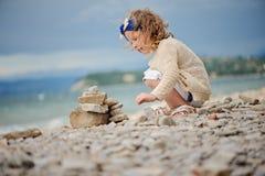 Torre encaracolado bonito da pedra de construção da menina da criança no lado de mar do verão Foto de Stock