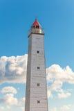 Torre grigia alta del faro con luce rossa Immagini Stock