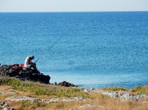 Torre Lapillo - Lonely fisherman. Torre Lapillo, Porto Cesareo, Puglia, Italy - July 21, 2016: a fisherman while preparing early in the morning line royalty free stock images