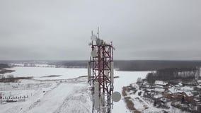 Torre móvil de la visión aérea con el plato de las antenas para la onda móvil en pueblo del invierno Torre de comunicación de la  almacen de video