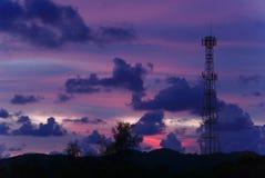 Torre mobile alta del telefono cellulare sull'alta collina che invia segnale collegare il persone in tutto il mondo nella sera in Fotografia Stock