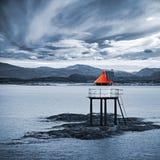 Torre norvegese rossa del faro sulle rocce del mare fotografia stock libera da diritti