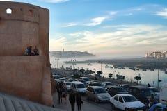 Torre, peatones y vehículos en las calles de Marruecos Foto de archivo