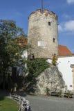 Torre redonda de piedra histórica con los bancos blancos por debajo ella Fotografía de archivo