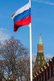 Torre roja de la Moscú el Kremlin cerca de la bandera rusa Imagen de archivo