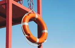 Torre vermelha do salvamento com uma corda de salvamento contra o céu azul Fotografia de Stock