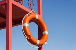 Torre vermelha do salvamento com uma corda de salvamento contra o céu azul Foto de Stock Royalty Free