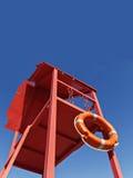 Torre vermelha do salvamento com uma corda de salvamento contra o céu azul Imagem de Stock