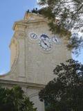 Torre vieja con el reloj, el calendario y las campanas de la iglesia de la pared Foto de archivo libre de regalías
