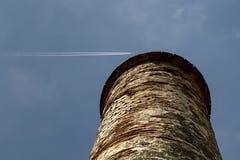 Torre vieja contra el cielo azul con los rastros de los aviones Foto de archivo libre de regalías