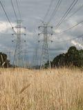 Torre y alambres de alto voltaje a través de la tierra del parque Imagen de archivo libre de regalías