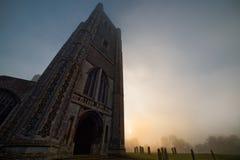 Torre y cementerio oscuros en Misty Sunrise Fotografía de archivo libre de regalías