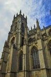 Torre y cielo nublado, azul, York, Inglaterra de la catedral Foto de archivo