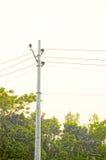Torre y línea eléctrica de alto voltaje de los posts en el cielo de la puesta del sol Fotografía de archivo