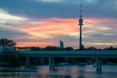 Torre y rascacielos sobre un río en la puesta del sol en Viena fotos de archivo