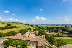 Torrechiara Castle in the Province of Parma, Emilia Romagna Italy. View of the castle and the landscape with sky, hills and rural dwellings around Torrechiara in royalty free stock photo