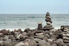 Torrecillas de piedra en la costa por el mar imagen de archivo