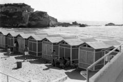 TORREGAVETA, NAPOLI, ITALIA, 1952 - i giovani bagnanti chiacchierano nella tonalità dello stabilmento balneare di Roman Beach pre fotografie stock libere da diritti
