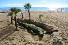 TORREMOLINOS, SPAGNA - 13 FEBBRAIO 2014: Un uomo che costruisce una grande scultura della sabbia con coccodrillo all'inizio della Immagine Stock