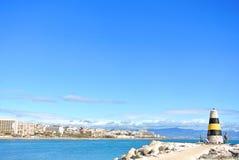 TORREMOLINOS, SPANJE - FEBRUARI 13, 2014: Een mening aan Middellandse Zee, een vuurtoren met golfbrekers en Torremolinos bij back Royalty-vrije Stock Foto