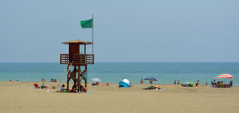 Torremolinos-Strand mit Feiertagsherstellern und Uhr ragen mit grüner Flagge hoch Stockbild