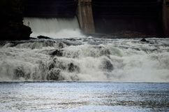 Torrent laiteux d'inondation de White River au-dessus de mur en béton en soleil d'été avec la centrale hydraulique à l'arrière-pl Image stock