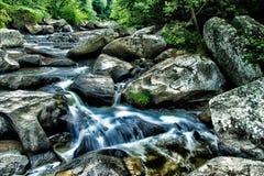Torrente montano con acqua che precipita a cascata sopra i massi Fotografia Stock