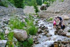 Torrente montano e due donne asiatiche con i loro bambini sulla riva rocciosa kazakhstan immagine stock