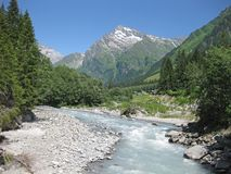 Torrential glacier milk river on a sunny day making its way to the valley. Glacier milk river on a sunny day making its way to the valley stock photos