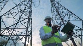 Torres altas de la electricidad y un técnico de sexo masculino que trabaja al lado de ellos almacen de video