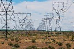 Torres da transmissão da linha elétrica do deserto alinhadas em seguido imagem de stock