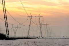 Torres de alta tensão da transmissão de energia no por do sol Fotografia de Stock