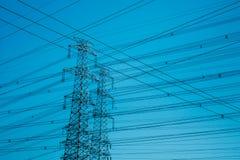 Torres de alta tensão mostradas em silhueta contra o azul fotos de stock