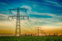 Torres de alto voltaje con los cables de transmisión colgantes gruesos en un l rural imagen de archivo