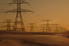 Torres de alto voltaje en fila en el postre en la puesta del sol imágenes de archivo libres de regalías