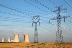 Torres de alto voltaje y central nuclear Fotografía de archivo libre de regalías