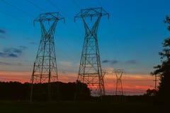 Torres de comunicación de cable de la electricidad en estirar de la puesta del sol fotos de archivo libres de regalías