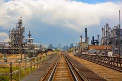 Torres de destilación de la refinería del petróleo y gas con pistas de ferrocarril y una ciudad distante Foto de archivo