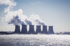 Torres de enfriamiento de una central nuclear o de un NPP con humo grueso en el cielo azul Foto de archivo libre de regalías
