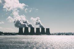 Torres de enfriamiento del NPP o de la central nuclear con humo grueso Imagen entonada oscura Imagen de archivo libre de regalías