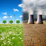 Torres de enfriamiento de una central nuclear en un paisaje devastado y turbinas de viento en un prado foto de archivo libre de regalías