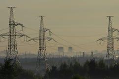 Torres de líneas eléctricas en la niebla del pre-amanecer imagenes de archivo
