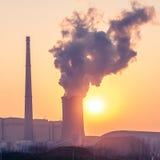 Torres de la chimenea y de enfriamiento de la central eléctrica durante puesta del sol Imagen de archivo