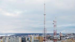 Torres de la telecomunicación en fondo del cielo nublado y paisaje urbano en día de invierno almacen de metraje de vídeo