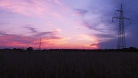 Torres de la transmisión de la electricidad en fondo de la puesta del sol Lapso de tiempo almacen de metraje de vídeo