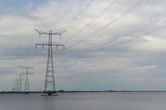 Torres de la transmisión en el río Fotos de archivo libres de regalías