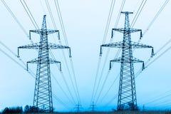 Torres de la tubería eléctrica en el campo del campo del invierno en el fondo del cielo azul y del bosque con los alambres imágenes de archivo libres de regalías