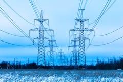 Torres de la tubería eléctrica en el campo del campo del invierno en el fondo del cielo azul y del bosque con los alambres imagen de archivo