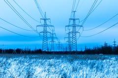Torres de la tubería eléctrica en el campo del campo del invierno en el fondo del cielo azul y del bosque con los alambres imagen de archivo libre de regalías