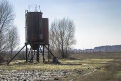 Torres del hierro para el agua en el campo Los tanques de almacenamiento del agua foto de archivo libre de regalías